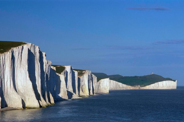 The Seven Sisters, the White Cliffs of Dover, a national landmark along the Kent coastline of the English Channel.  Steep white chalk cliffs on the shore, dropping down into the sea.